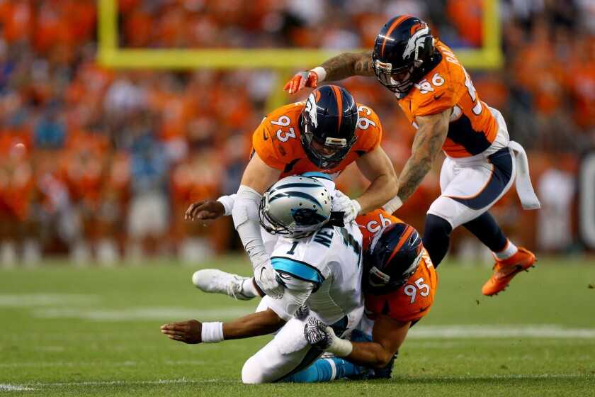 Panthers quarterback Cam Newton (1) is hit by Broncos defenders Derek Wolfe (95) and Jared Crick (93) in the first quarter at Sports Authority Field at Mile High.