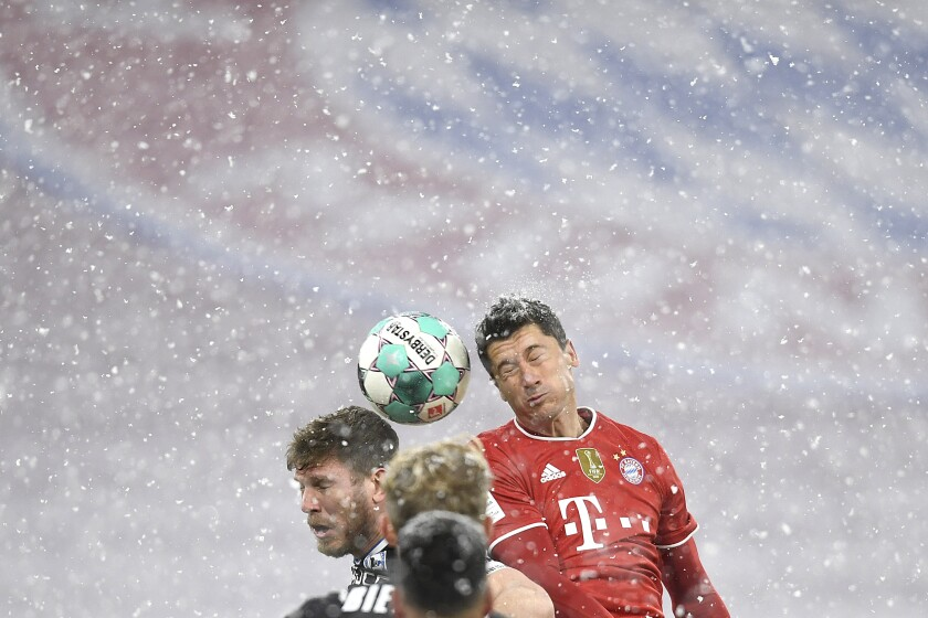 Bayern's Robert Lewandowski, right, jumps for the ball with Arminia's Manuel Prietl during a German Bundesliga soccer match between Bayern Munich and Arminia Bielefeld at the Allianz Arena in Munich, Germany, Monday, Feb. 15, 2021. (AP Photo/Andreas Schaad, Pool)