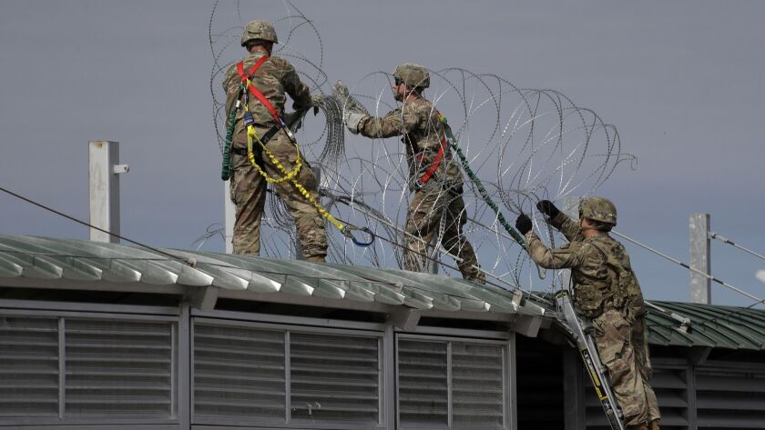 Members of the U.S.military place razor wire along the U.S.-Mexico border on the McAllen-Hidalgo Int