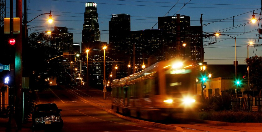 A Metro Gold Line train travels east from the city center as dusk descends on Los Angeles.