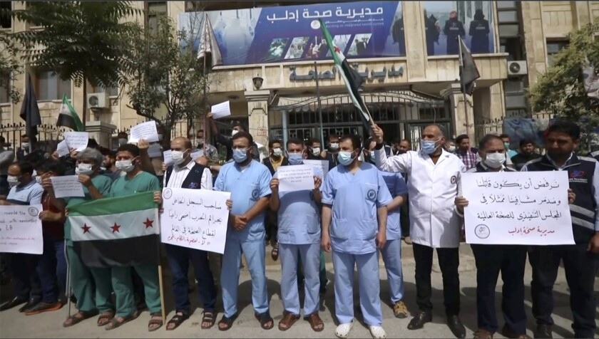 In this image taken from video, dozens of medical workers protest a decision to grant Syrian President Bashar Assad's government a seat on the executive board of the World Health Organization, Monday, May 31, 2021, in Idlib, Syria. (AP Photo)