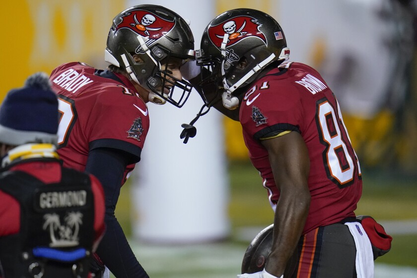 Tampa Bay Buccaneers quarterback Tom Brady (12) and wide receiver Antonio Brown (81) celebrate a touchdown pass during the first half of an NFL wild-card playoff football game against the Washington Football Team, Saturday, Jan. 9, 2021, in Landover, Md. (AP Photo/Julio Cortez)