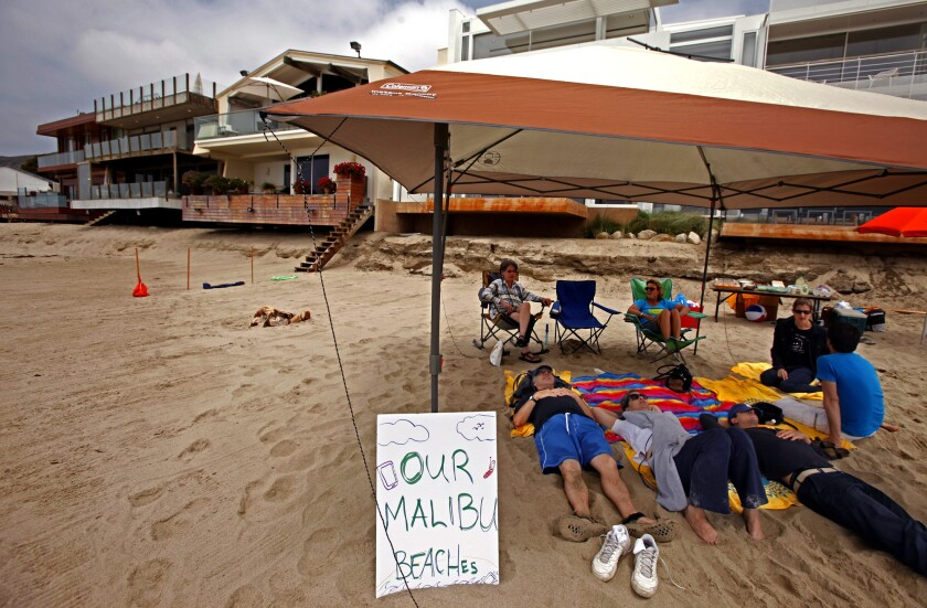Jenny Price, seated in chair, left, and Ben Adair, wearing a blue T-shirt, are joined by friends on a stretch of beach in Malibu.