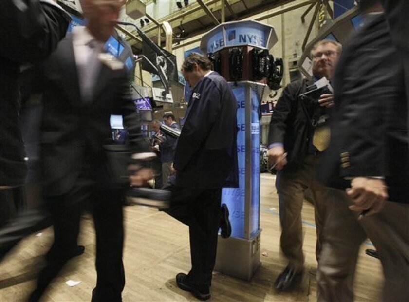 In this June 7, 2010 photo, a trader leans on a phone post as he works on the floor of the New York Stock Exchange, in New York. Stocks are looking for direction Tuesday, June 8, after another late-day plunge sent the Dow Jones industrial average to its lowest level in seven months. Stock futures rose slightly.(AP Photo/Richard Drew)