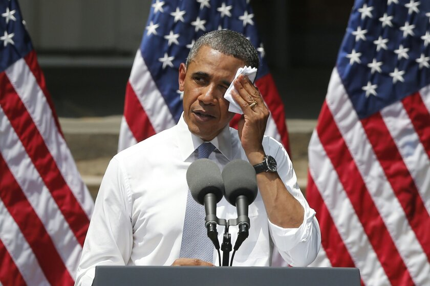 FILE - This June 25, 2013 file photo shows President Barack Obama wiping perspiration from his face as he speaks about climate change at Georgetown University in Washington. The Obama administration is poised to unveil first-ever rules limiting greenhouse gas emissions from the power plants that do