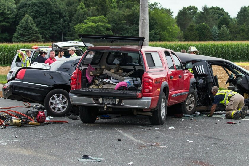 "FILE - This July 18, 2015 file photo shows authorities investigating the scene of a fatal crash between a limousine and sports utility vehicle in Cutchogue, N.Y. A New York prosecutor says a misdemeanor DWI charge remains in effect ""at this time"" for the pickup truck driver who police say slammed into a limousine in Long Island wine country, leaving four women dead and four others injured. (Randee Daddona/Newsday via AP, File)"