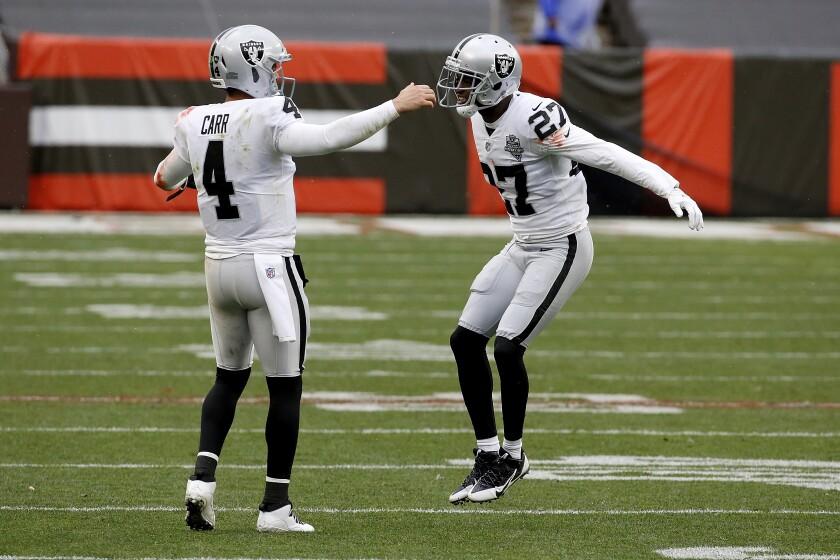 Quarterback Derek Carr congratulates cornerback Trayvon Mullen after the Raiders defense made a stop against the Browns.