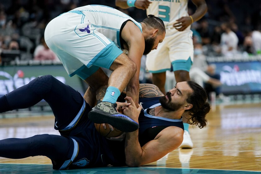 Charlotte Hornets forward Cody Martin and Memphis Grizzlies' Steven Adams struggle to get possession of the ball during the first half of a preseason NBA basketball game Thursday, Oct. 7, 2021, in Charlotte, N.C. (AP Photo/Chris Carlson)