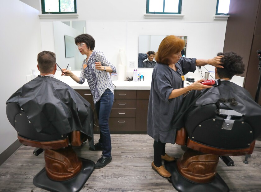 Brian Popp, seated at left, gets a haircut from volunteer stylist Ana Maria Creasywhile Mary Calao gets her hair styled by volunteer Esther Schulz in the new Village Clips Barber Shop for homeless people in the Joan Kroc Center at Father Joe's Villages.