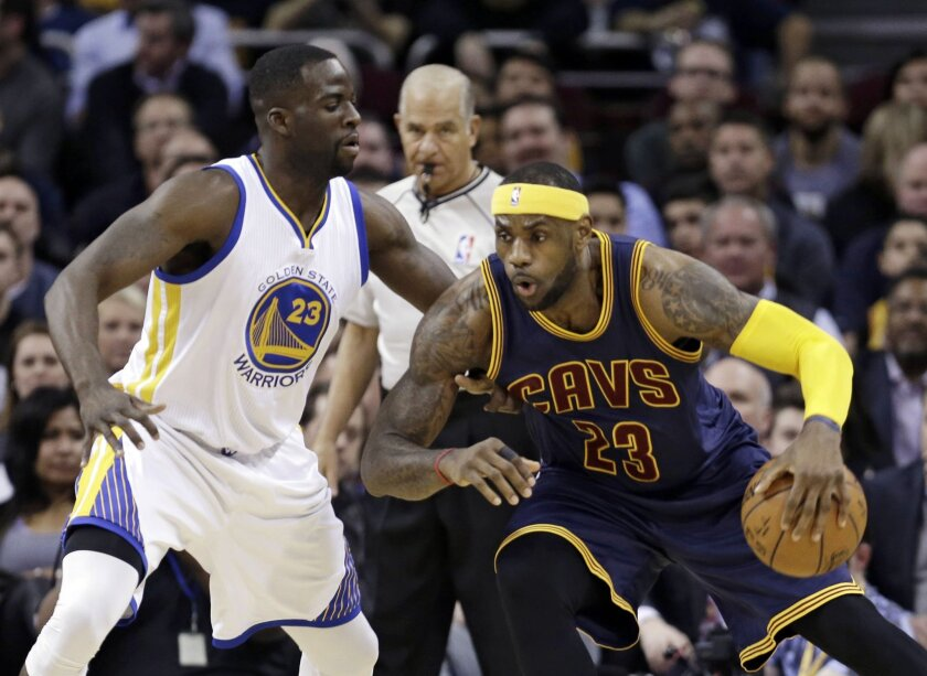 Cleveland Cavaliers' LeBron James, right, drives past Golden State Warriors' Draymond Green during the first quarter of an NBA basketball game Thursday, Feb. 26, 2015, in Cleveland. (AP Photo/Tony Dejak)