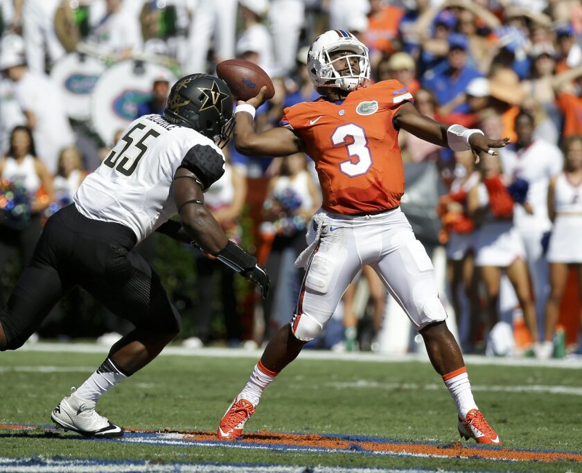 Florida quarterback Treon Harris (3) throws a pass as he is pressured by Vanderbilt defensive end Caleb Azubike (55) during the first half of an NCAA college football game, Saturday, Nov. 7, 2015, in Gainesville, Fla. (AP Photo/John Raoux)
