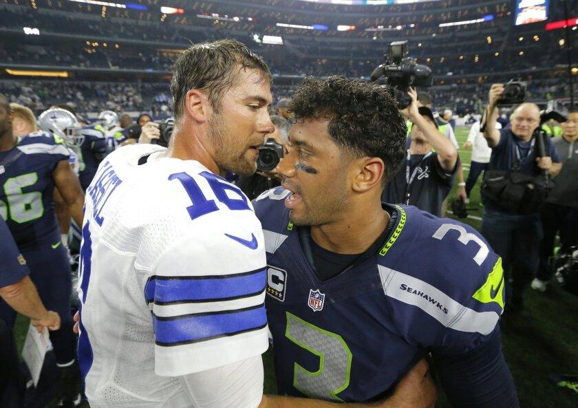Dallas Cowboys' Matt Cassel (16) talks with Seattle Seahawks' Russell Wilson (3) after an NFL football game Sunday, Nov. 1, 2015, in Arlington, Texas. The Seahawks won 13-12. (AP Photo/Brandon Wade)