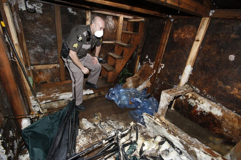 Sergeant Peter Horvath from the King County Sheriff's office inspects the mold-covered vault, Tuesday, March 10, 2015, near Lake Sammamish, Wash. On a wooded hillside east of Lake Sammamish, the U.S. attorney and the FBI held a joint tour of an underground survivalist bunker belonging to Bradley St