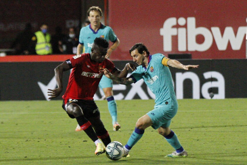 Barcelona's Lionel Messi, right, vies for the ball with Marllorca's Iddrisu Mohamed Baba during the Spanish La Liga soccer match between Mallorca and FC Barcelona at Son Moix Stadium in Palma de Mallorca, Spain, Saturday, June 13, 2020. With virtual crowds, daily matches and lots of testing for the coronavirus, soccer is coming back to Spain. The Spanish league resumes this week more than three months after it was suspended because of the COVID-19 pandemic. (AP Photo/Francisco Ubilla)