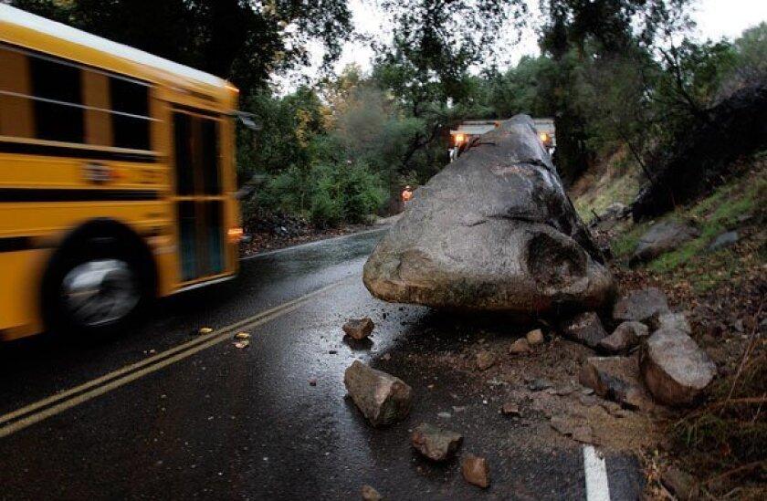 An eight-foot-diameter boulder fell down a hillside onto Mussey Grade Road south of Dos Picos Road near Ramona and blocked a lane. (John Gastaldo/The San Diego Union-Tribune)