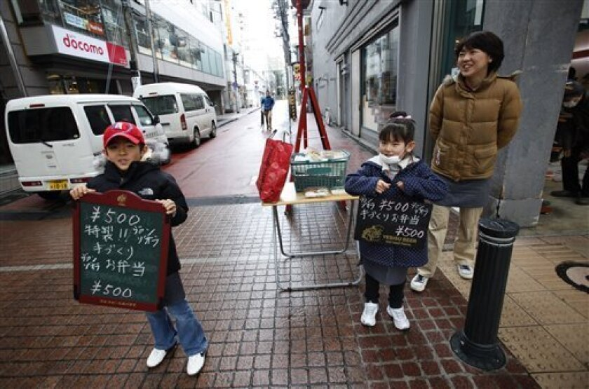 Taiyo Sawada, from left, and Maria help their mother Miyuki sell lunch outside their restaurant in Sendai, Miyagi Prefecture, northern Japan, Saturday, March 26, 2011, following the March 11 earthquake, tsunami and the subsequent crisis at the Fukushima Dai-ichi nuclear complex. Their restaurant resumed its services outside of the restaurant as its inside still remain devastated by the quake and tsunami. (AP Photo/Shizuo Kambayashi)