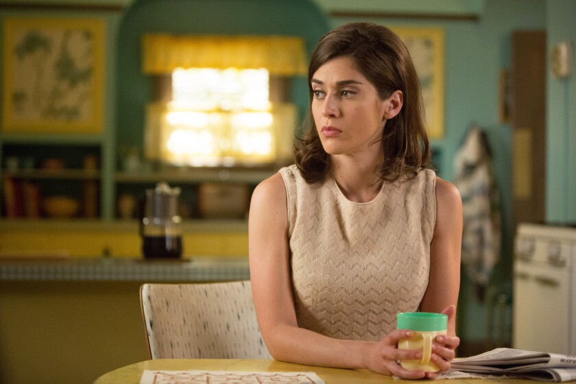 """In Showtime's """"Masters of Sex,"""" researcher Virginia Johnson, played by Lizzie Caplan, has a vibrant yellow and teal kitchen circa 1966, complete with cafe curtains and cabinets with floral paper insets from Astek Wallcoverings."""