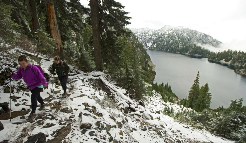 FILE - In this Nov. 3, 2015, file photo, Kasee Palmer, left, and Summer Sturhan, both of Olympia, Wash., hike on Snow Lake Trail above Snoqualmie Pass in Washington state, as some of the first snow of the season fell in the area. Mountain snowpack came in above normal in Washington state, raising h