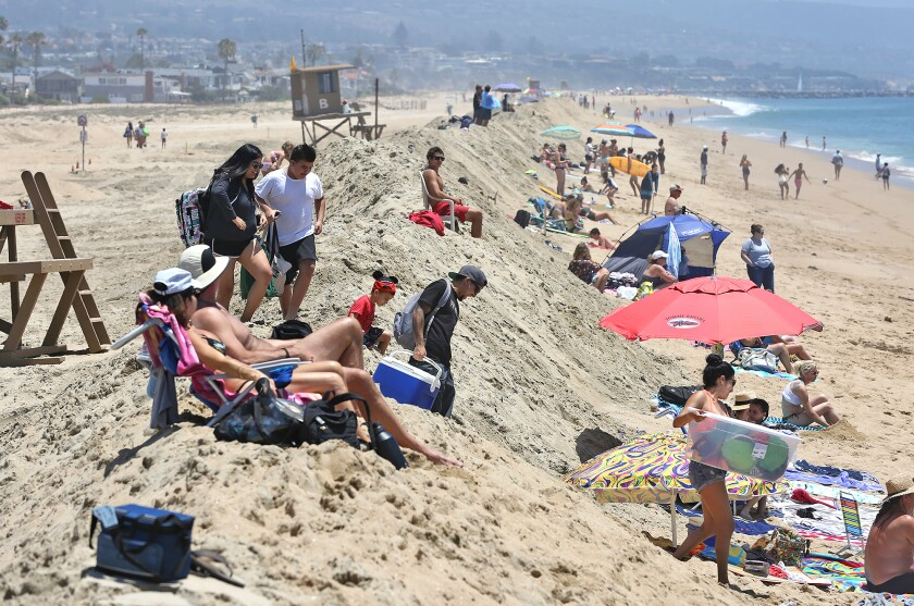 Beachgoers climb and sit on top of a sand berm that was rebuilt to hold off big waves and high tides at Balboa Pier.