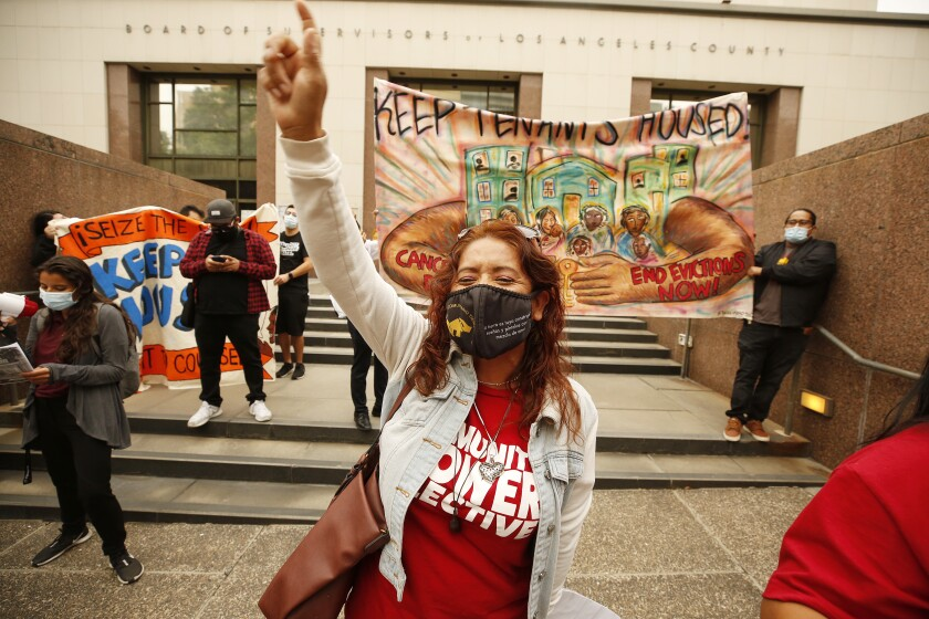 """A protester points to the sky while other protesters hold a banner that reads: """"Keep tenants housed."""""""