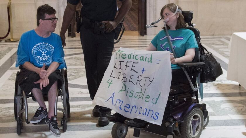 Protesters opposed to the Republican-crafted Senate healthcare bill are arrested by Capitol Police outside the office of Senate Majority Leader Mitch McConnell (R-Ky.) on Thursday.