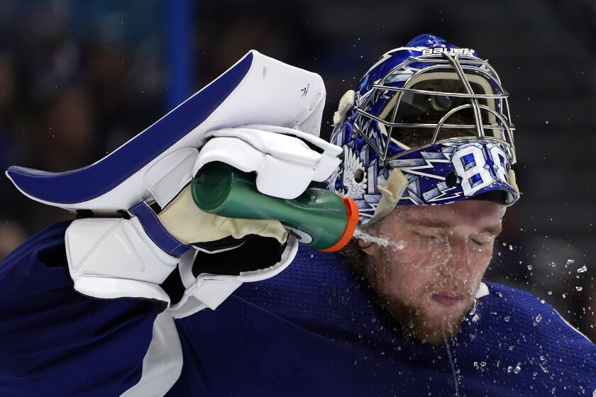Tampa Bay Lightning goaltender Andrei Vasilevskiy (88) sprays water on his face during the third period in Game 1 of an NHL hockey Stanley Cup semifinal playoff series against the New York Islanders Sunday, June 13, 2021, in Tampa, Fla. (AP Photo/Chris O'Meara)