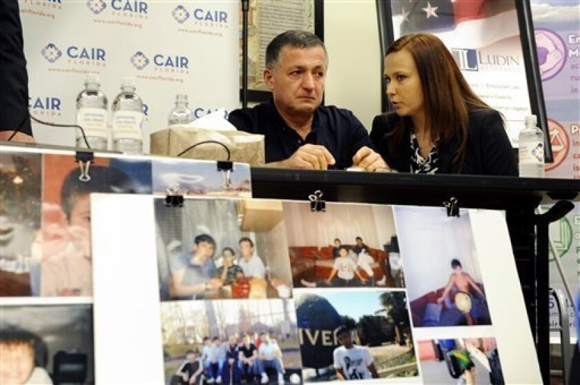 Abdulbaki Todashev, left, the father of Ibragim Todashev, listens, through interpreter Viktoryia Johnson, as his attorneys describe their quest for information into the shooting death of Ibragim during a press conference at an office for the Council on American-Islamic Relations Florida (CAIR Florida) on Tuesday, Aug. 13, 2013, in Tampa, Fla. Ibragim Todashev, 27, was shot and killed on May 22, 2013, while being questioned by law enforcement inside an apartment in Orlando, Fla. (AP Photo/Brian B