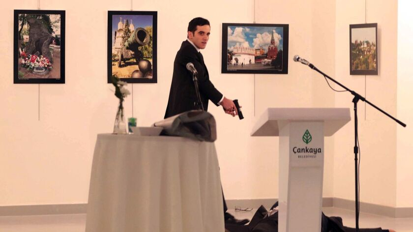 A gunman, later identified as off-duty police officer Mevlut Mert Altintas, shouts after shooting Russia's ambassador to Turkey, Andrei Karlov, at a photo gallery in Ankara, Turkey, on Dec. 19, 2016.