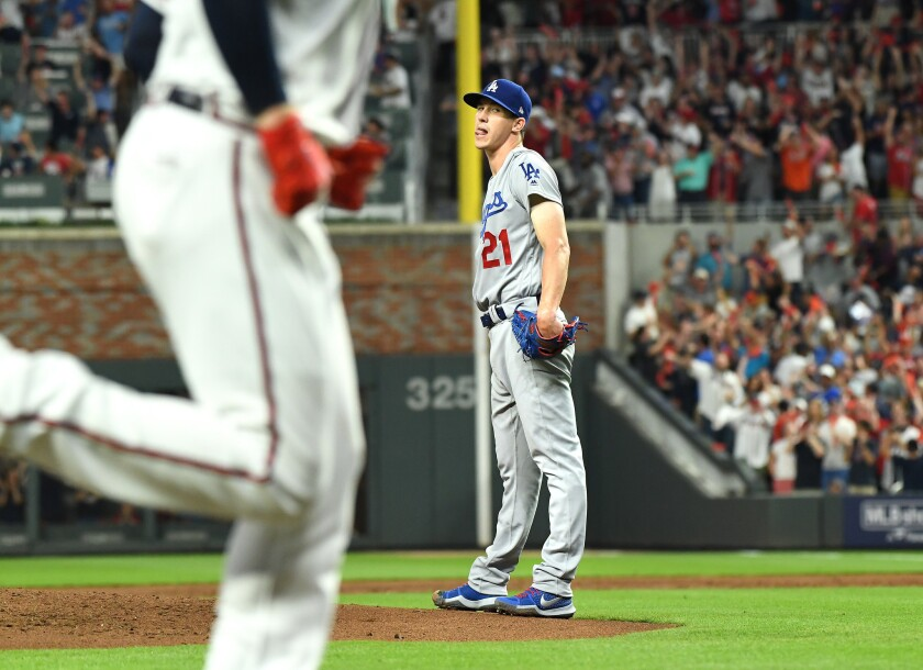 Dodgers pitcher Walker Buehler can only watch as Ronald Acuna Jr. hits a grand slam in the second inning on Sunday.