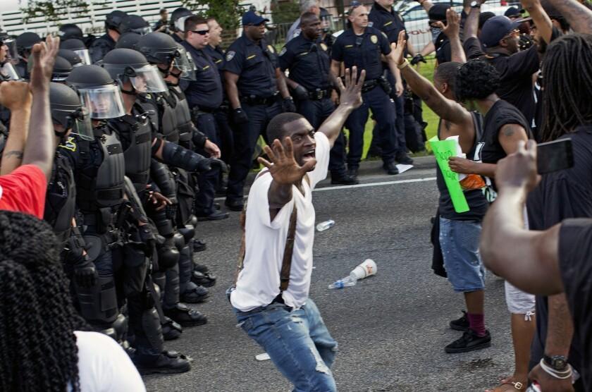 Un hombre intenta impedir que manifestantes se enfrenten a policías antimotines ante la comisaría de policía de Baton Rouge, luego de la policía intentara despejar la calle, en Baton Rouge, Louisiana, el 9 de julio de 2016. Varios manifestantes fueron detenidos. (AP Foto/Max Becherer)