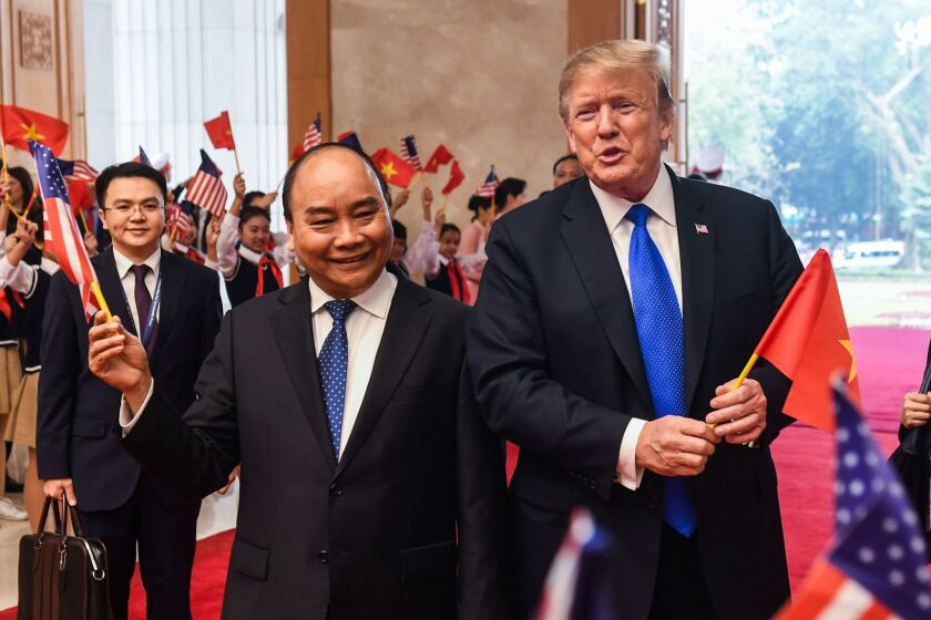 President Donald Trump holds a Vietnamese flag as Vietnam's Prime Minister, Nguyen Xuan Phuc, waves a U.S. flag upon their arrival for a meeting in Hanoi on February 27, 2019,.