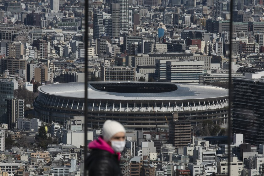 """In this March 3, 2020, photo, the New National Stadium, a venue for the opening and closing ceremonies at the Tokyo 2020 Olympics, is seen from Shibuya Sky observation deck in Tokyo. Japan's Olympic minister has suggested in Parliament that the Tokyo Olympics might be pushed back a few months from it July 24 opening. The games are under threat from a spreading virus from China that has reached the pandemic stage. But the so-called """"Home City Contract""""signed by the International Olympic Committee and Japanese officials gives the IOC wide latitude in terminating the Olympics. (AP Photo/Jae C. Hong)"""