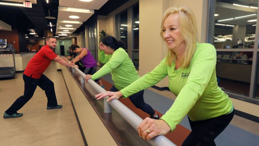 Beth Thorp, foreground, works out with other members of the Lucky 13 team while trainer Paul Carey, left, looks on at Tri-City Wellness Center in Carlsbad.