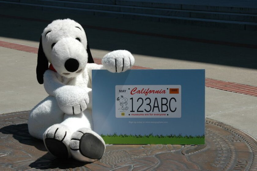 """Snoopy sits at the state Capitol with a prototype of the specialized plate that reads """"Museums are for everyone."""""""