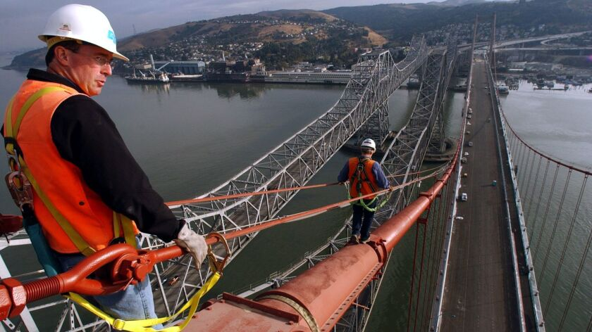 Construction Manager Steven Whipple, left, looks over the bay from a height of 420 feet as Bridge En