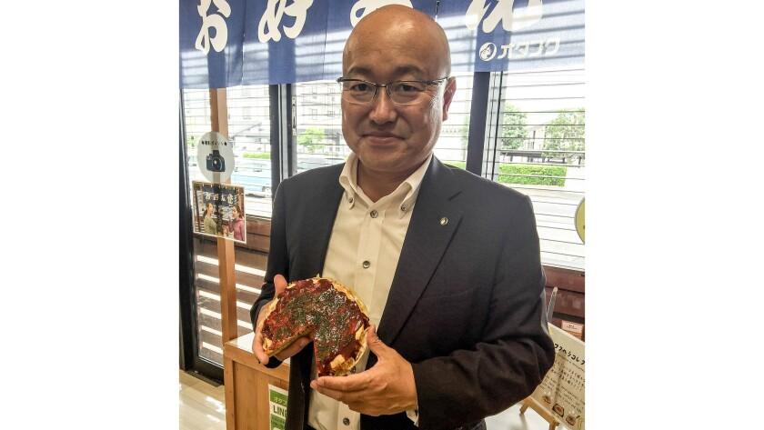 Otafuku Sauce Co. President Naoyoshi Sasaki, holding a plastic model of okonomiyaki used in shop windows.