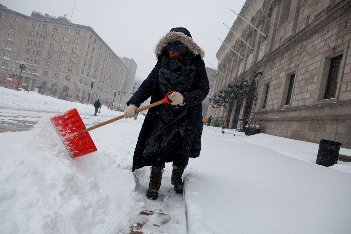 A library employee works to clear the sidewalks in front of the main branch of the Boston Public Library in Boston on Tuesday.