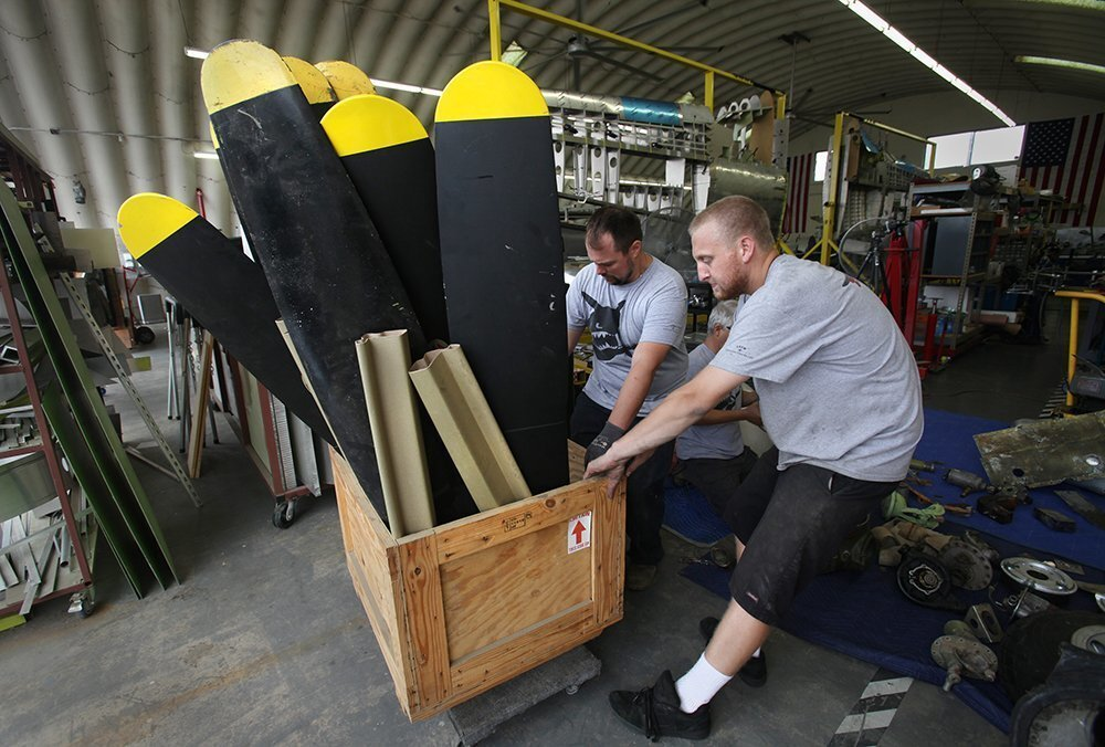 Cole Meek, foreground, who just graduated from West Hills High, and Dan Smith, move a crate of propellers to make more room for assembling the nose of a plane.
