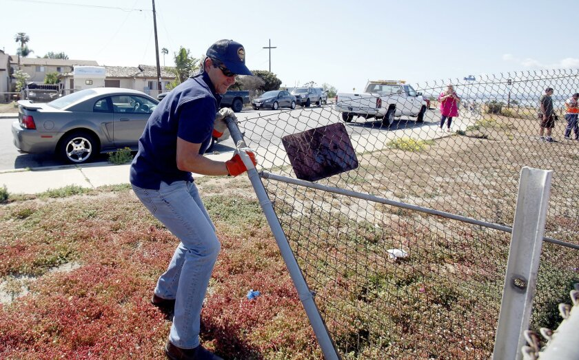 Imperial Beach Mayor Serge Dedina removes a chain-link fence near 12th Street and Boulevard Avenue in I.B. on May 25.