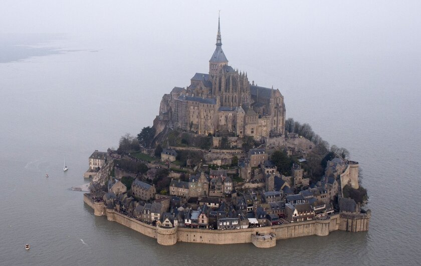 FILE - In this March 21, 2015 file photo, a high tide submerges a narrow causeway leading to the Mont Saint-Michel, on France's northern coast. This offshore islet topped by a stunning 8th century Benedictine abbey was France's first heritage site and among the first ever designated. Already a major pilgrimage destination in the Middle Ages, it underwent many transformations but has always drawn romantics and the faithful, even when it served as a prison during the French Revolution. (AP Photo) FRANCE OUT