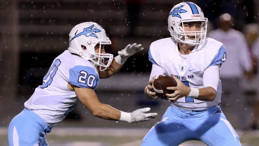 Corona Del Mar football QB #4 Ethan Garbers hands off to #20 Jason Vicencio as rain comes down in aw
