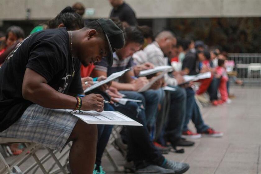 Migrantes llenan solicitudes de trabajo durante la inauguración de una feria del empleo hoy, viernes 5 de octubre de 2018, en la ciudad de Tijuana, en el estado de Baja California (México). EFE