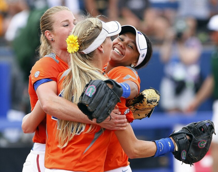 Florida pitcher Hannah Rogers, Taylor Schwarz, front, and Kelsey Stewart, right, celebrate after defeating Baylor during an NCAA women's softball College World Series tournament game, Sunday, June 1, 2014, in Oklahoma City. Florida won 6-3. (AP Photo/Alonzo Adams)
