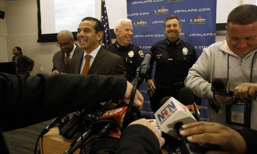 Mayor Antonio Villaraigosa and LAPD Chief Charlie Beck, second from right, smile before the news conference Monday announcing the new staffing level at the Police Department.