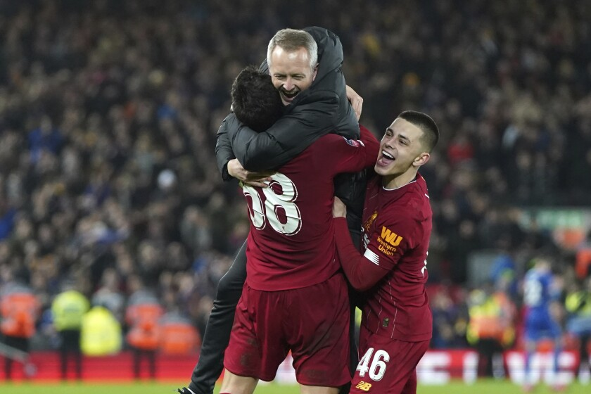 Liverpool's Under 23 coach Neil Critchley, center, celebrates with Liverpool's Pedro Chirivella and Liverpool's Adam Lewis, right, after winning the English FA Cup Fourth Round replay soccer match between Liverpool and Shrewsbury Town at Anfield Stadium, Liverpool, England, Tuesday, Feb. 4, 2020. Liverpool won 1-0. (AP Photo/Jon Super)
