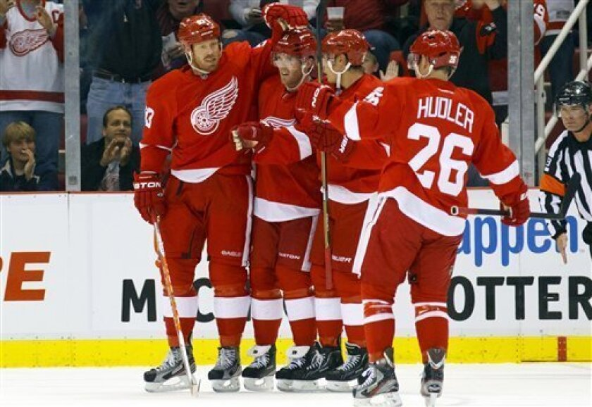 Detroit Red Wings left wing Johan Franzen, left, of Sweden, celebrates with Red Wings forward Danny Cleary, second from left, and other teammates after scoring his second goal in the first period of an NHL hockey game against the Columbus Blue Jackets in Detroit, Friday, Oct. 21, 2011. (AP Photo/Ri