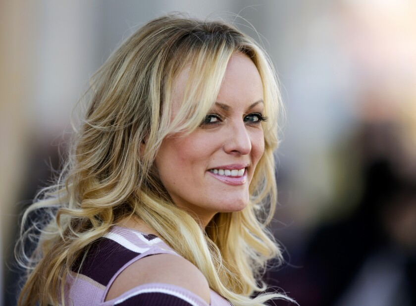 FILE - In this Oct. 11, 2018, file photo, adult film actress Stormy Daniels attends the opening of the adult entertainment fair 'Venus' in Berlin, Germany. Ohio's capital city has reached a $450,000 settlement with Stormy Daniels over the porn actress' arrest at a strip club last year. Her federal defamation lawsuit against several Columbus officers alleged officers conspired to retaliate against her over her claims that she had sex with Donald Trump before he became president. (AP Photo/Markus Schreiber, File)