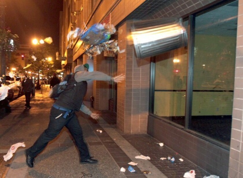 A man in Oakland throws a trash can at the window of a building during a protest after George Zimmerman was found not guilty in the shooting death of teenager Trayvon Martin.