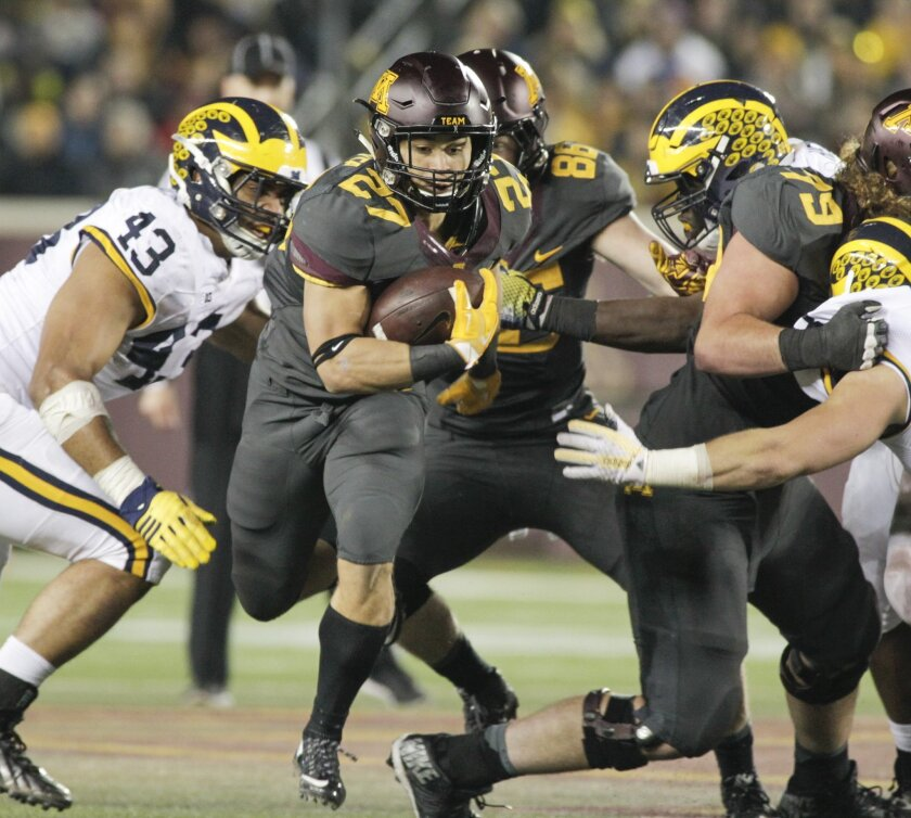 Minnesota running back Shannon Brooks (27) runs for eight yards during the first half of an NCAA college football game Saturday against Michigan, Nov. 31, 2015, in Minneapolis.(AP Photo/Paul Battaglia)