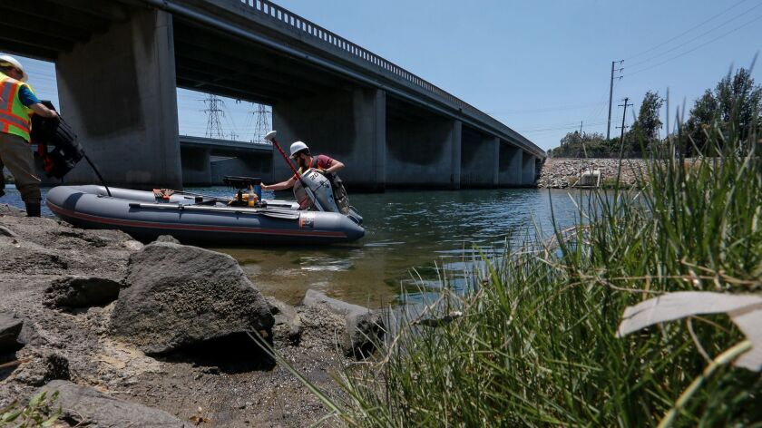Caltrans student assistant Rami Gharaibeh prepares a small inflatable boat with bridge engineer Kevi